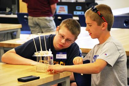 Austin Malone and Cameron Beavers contemplate on what they should do to their tower next. 