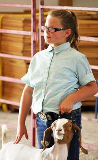 Chevy Vaske stands in formation as she waits to be judged on her market goat at the 4-H Open Market Goat Show on July 31.