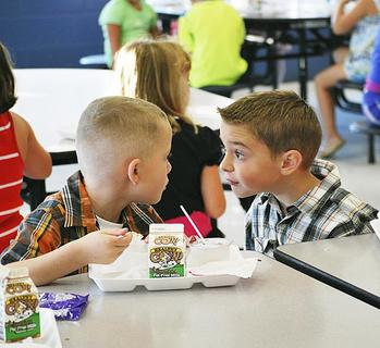 Mason-Corinth Elementary students Collin Hollingsworth, left, and Johnny Scherder, right, discuss the first day of school over lunch.