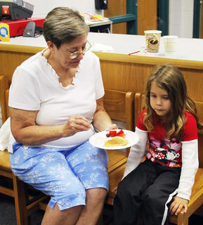 Patsy Henry shares a pancake and some strawberries with her granddaughter, Emily Henry at breakfast.