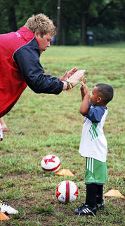 Alex Bent, Challenger Soccer Coach, gives Desnond Davis a high five for a job well done.