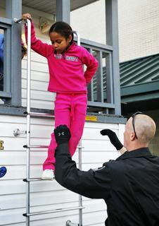 Officer Mattt Boshears helps MCE student Kiana Cook down from the ladder after learning the dangers of fire.