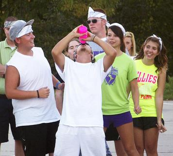 WHS students Jared Hicks, Cierra Staub, Andrea Carter and Quade Simpson watch as Dustin Davis guzzles a water bottle at the senior picnic.