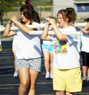 lyssa Rose and Autumn Ellis practice keeping their arms in formation with light-weight pipes.
