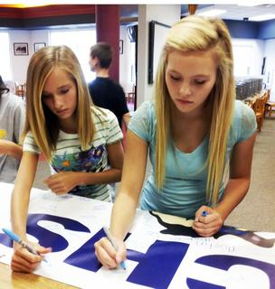Grant County High School freshmen Mikayla Bowen, left, and Hannah Rose sign a banner promising they will graduate.