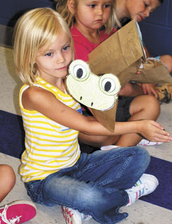 Peyton Walters follows along with her classmates, as they do a routine with their frog puppets.