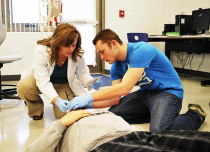 Sherry Lawson, GCHS health and science teacher, helps Daniel Rice assess Tyler Caudill's 'eye injury' in class.