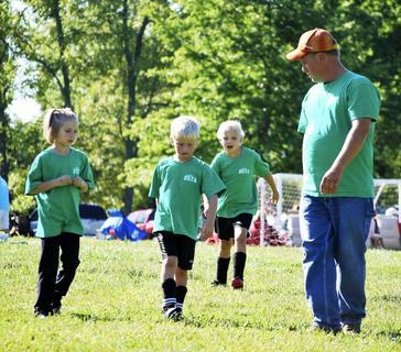 Greg Traylor, assistant coach of the Green Machine U8, shows Taylor Franklin, Boston Traylor and Ashlynn Slaughter where they should be on the field.
