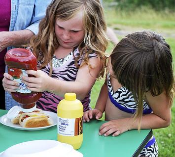 Abigail Hopkins puts ketchup on her hotdog while her sister, Hailey Hopkins watches.