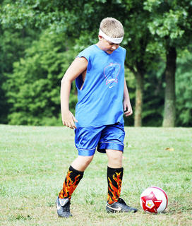 Kyler Harvey focuses hard on kicking the ball.