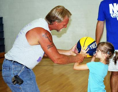 Larry Martin, an assistant to the coaches, shows Audrey Shelton the proper way to hold a basketball.