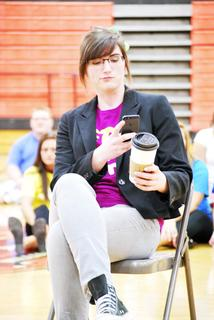 Cassidy Clayton drinks her Starbucks and texts on the phone as part of her act while the crowd bids.