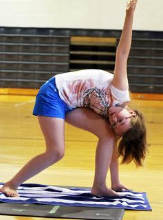 Mikayla Goerler tries to stretch all her muscles in a yoga postiton.