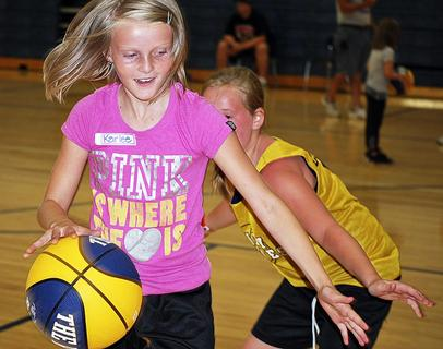 Abby West dribbles while McKenzie Clemons tries to get the basketball from her.
