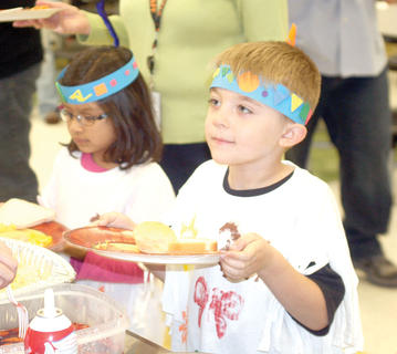 Kindergartner Holten Schultz holds his plate up for more turkey. 