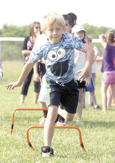 Cody McNay leaps the hurdles during a race at WES's track and field day.