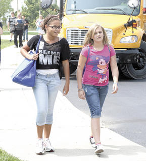 Williamstown Middle School sixth graders McKenzie Johnson and Hailee Roland walk to their bus.