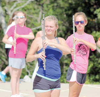 Sommer Easterwood and Amber Tien practice marching with their flutes during summer band camp at WHS.