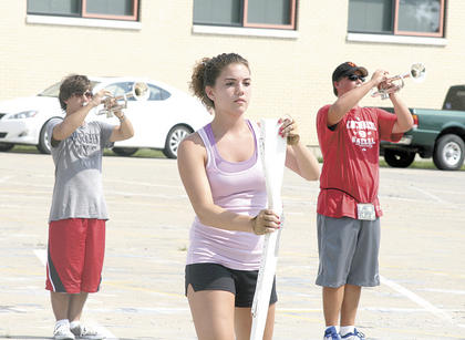 Morgan Threlkeld, center, practices twirling her rifle while Dustin Davis, left, and Derek Cummins, right, play their instruments during the WHS Band of Spirit band camp.