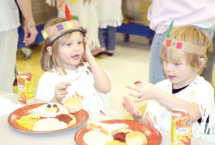 Kindergartners Josie Kumler and Madison Whitworth talk about what they are thankful for over their Thanksgiving meal.