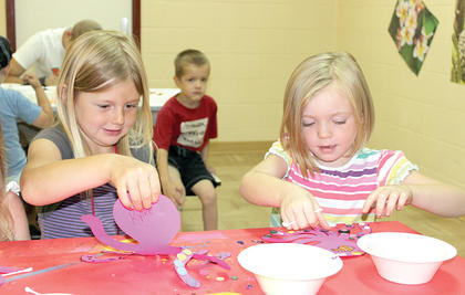 Kylee Webster, left, and Cassie Nichols, right, show off their craft during VBS.