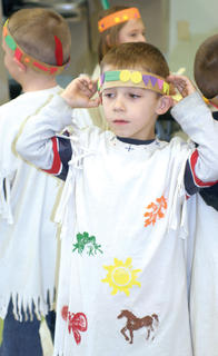 Kindergartner Ethan Webster adjusts his headdress as he waits in line. 