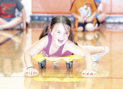WES kindergartner Gracie Button slides on her belly during a relay race at track and field day. 