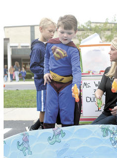 Cayden Smithers, dressed as Superman, shoots a water gun into a pool during a game.