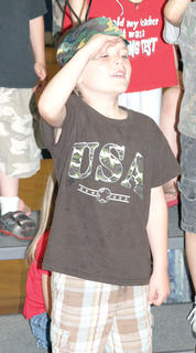 Benjamin Carr salutes while wearing a camouflage hat as an Army ant during the play.