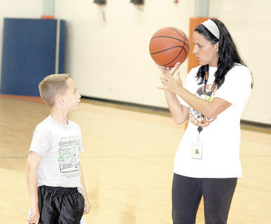 WHS girls' basketball coach Kasey Kennedy shows Spencer Stephens the proper technique to shoot a ball during basketball camp.