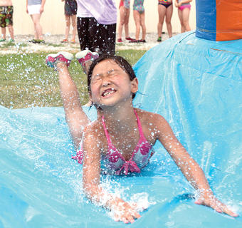 Gracie Deatherage makes water fly as she splashes down the slip and slide. Photo by Bryan Marshall