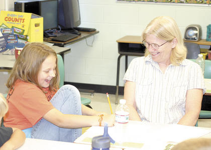 Kylie Holt laughs with her grandmother, Ruth Eddie as she draws on paper at Grandparents Day.