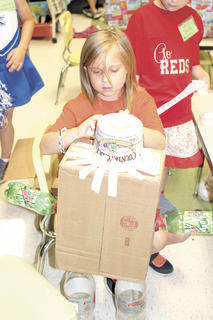 Kaylee Bonar works on constructing her own robot using a cardboard box, a butter container, Mountain Dew bottles and tape.