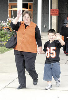 Kindergarten student David Souder and his grandma wave as they start a walk in front of the school.
