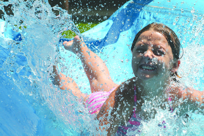Jadyn Shaw didn't mind taking the plunge on Monday, July 21 at the Corinth Park as temperatures climbed into the 90s. Grant County Parks and Recreation brought inflatable waterslides to the park. Photos by Seth Graham