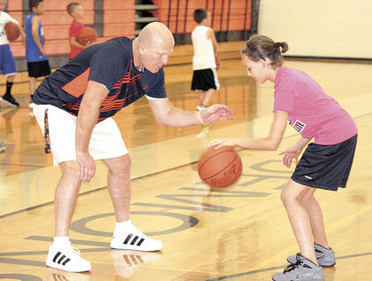 New WHS boys' basketball coach Roger Harden teaches Ryan Parsons dribbling skills at the Mad Skills Basketball Camp at the school. Harden, a former UK player, invited Kenny Walker and others to speak to campers.