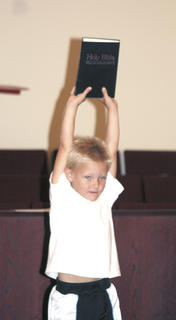 Dylan Farmer holds up the Bible for everyone to see at Crittenden Baptist VBS.