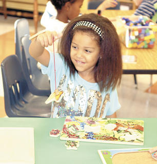 Williamstown Elementary kindergartner Alyssa Carr smiles as she picks up a puzzle piece during the first day of class. Photo by Bryan Marshall