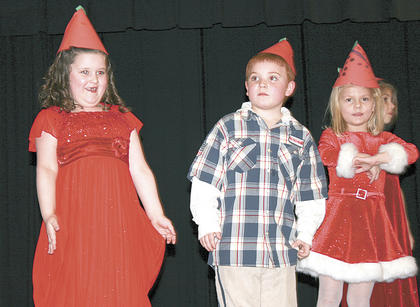 Williamstown Elementary students Heaven Hall, Christian Perry and Lexie Wilson show their outfits off on stage during the Christmas concert.