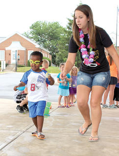 Caitlyn Treichel helps Khalid Lewis as he runs a water relay while wearing goggles.