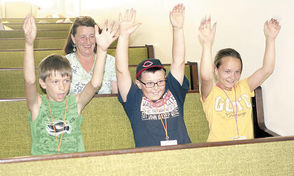Kyle Stephens, Jacob Hughes and Bekah Letner raise their arms while performing a dance at God's Community Church Vacation Bible School.