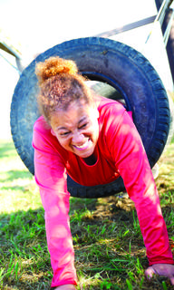 Rose Arnell crawls through a tire.
