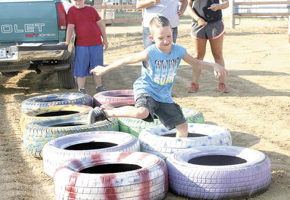 Noah Toomey jumps over tires during an obstacle course at Childrens Fun Night at the fair. Photo by Bryan Marshall