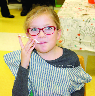 Isabelle Martin takes a big bite during the annual Thanksgiving feast at Williamstown Elementary.