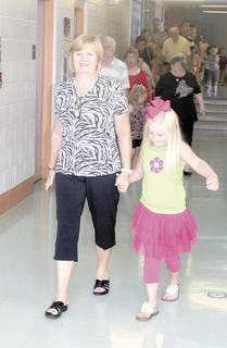 Judy West holds her granddaughters hand, Sophie Kightlinger, as they walk down the hall together.