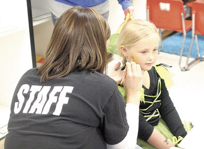 CMZ kindergartner Joie Ginder adds to her costume with face paint.