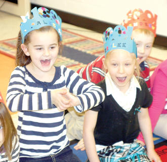 WES kindergartners Alexis Day, left, and Kaylee Taylor, right, cheer as the class makes a 100-inch snake.