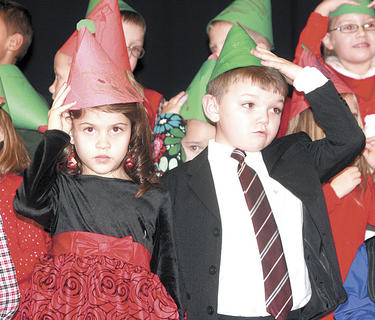 Emma Stevens and Cayden Smithers hold their elf hats up during the concert.