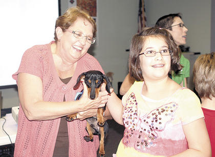 Grant County Library childrens' librarian Cheryl Clemons holds a wiener dog while Ava Herrmann pets Wally, who is the brother of Woody, featured in Kentucky author Leigh Anne Florence's popular book series.