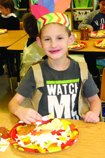 Bentley Niesen smiles for the camera while eating his meal and wearing a homemade headpiece.